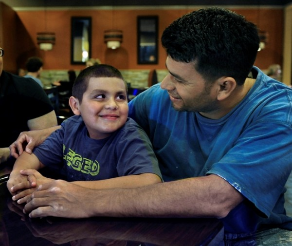 German Morales visits with his son Alejandro, 8, at the Oakton, Va., restaurant where his wife, Iliana, and older son, Christian, 16, work. Iliana waits tables, and Christian is a busboy -- and for both, those are second jobs. Illustrates