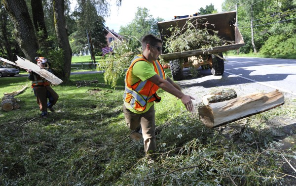 "Brewer Public Works laborers Bobby Coombs (right) and Casey Brooks (left)  remove tree debris from Dwinal Rideout's front lawn off North Main St. in Brewer Monday morning, Aug. 29, 2011. A large branch on Riedout's 60-year-old weeping willow gave way around 11:30 pm Sunday as tropical storm Irene's winds continued to batter much of Maine. Rideout, 82, has lived at the house since 1957 and remembers another storm destroying his roof in the early 1960's. ""I'm very lucky. The branch could have fallen the other way,"" said Rideout."