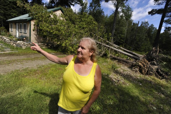 Dale Nickerson walks around her tree-damaged home Monday morning while recounting how winds from Tropical Storm Irene ripped through her neighborhood on Davis Pond in Holden.