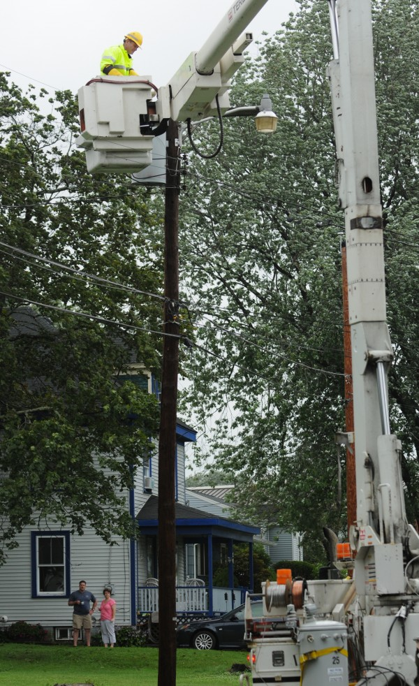 Bangor Hydro lineman Dan Anxien trips a breaker on a transformer on Vine Street in Bangor to restore power as neighbors watch on Sunday August 28, 2011.