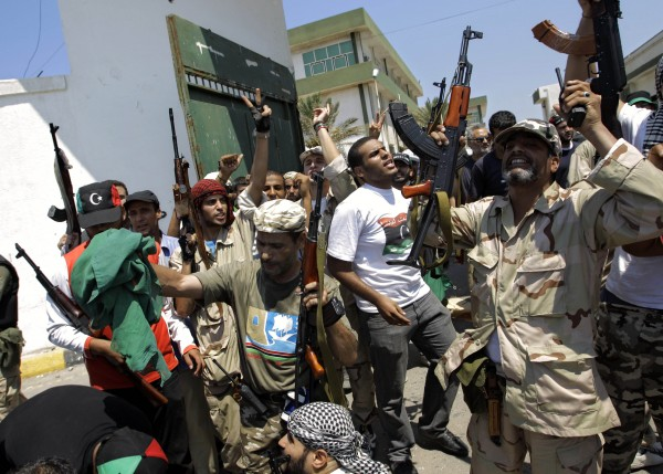 Libyan rebel fighters gesture at the former female military base in Tripoli, LIbya, Monday, Aug. 22, 2011.