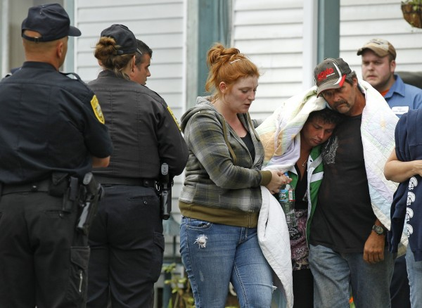 New Hampshire State Police officers watch as a woman identified by the NH Attorney General's office as Celina Cass' mother, under blanket, is escorted from the family home in Stewartstown, N.H., Wednesday, July 27, 2011. Cass, 11, who disappeared almost a week ago was discovered Monday, Aug. 1, in a river less than half a mile from her home, authorities said. The death was being considered suspicious.