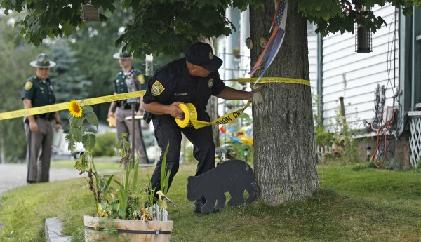 A New Hampshire State Police Trooper puts crime scene tape around the family home of Celina Cass in Stewartstown, N.H., Wednesday, July 27, 2011. Cass, 11, who disappeared almost a week ago was discovered Monday, Aug. 1, in a river less than half a mile from her home, authorities said. The death was being considered suspicious.