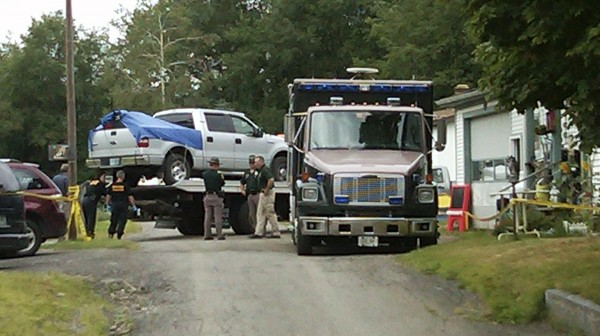 This cell phone photo shows law enforcement officials standing near a silver pickup truck being removed from where it was parked near the home of Celina Cass, in Stewartstown, N.H., Wednesday, Aug. 3, 2011. Cass, 11, had been missing for a week before her body was found nearby in the Connecticut River, on Monday.