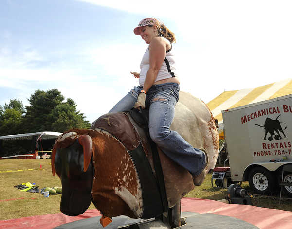 Rebecca Daoust of Tilton, N.H., rides a mechanical bull during the inaugural Redneck Olympics in Hebron on Saturday.