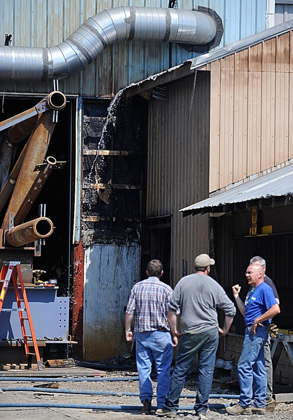 Workers with Newport Industrial Fabrication, Inc. waited outside the plant as firefighters inside doused a fire that spread inside a wall Friday, Aug. 19, 2011. The fire was extinquished in several minutes. No one was injured and the damage was minimal.