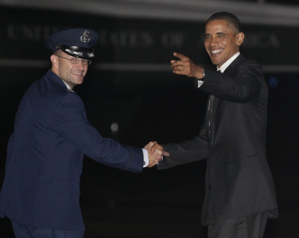 President Barack Obama turns with Col. Kenneth Rizer to listen to members of the media and crew sing him Happy Birthday on the tarmac as he arrives from Chicago on Air Force One, Thursday, Aug. 4, 2011, in Andrews Air Force Base, Md.