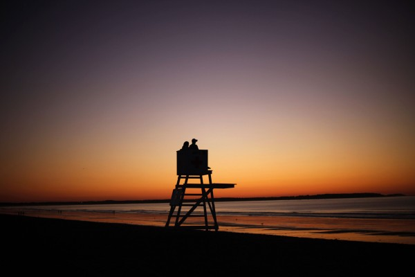 A couple waits for the sunrise on a lifeguard's tower at dawn at Old Orchard Beach.
