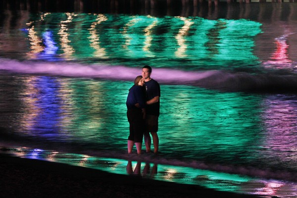 The colorful lights of The Pier reflect on the surf as a couple shares a quiet moment at night at Old Orchard Beach.