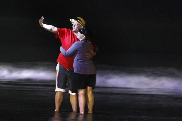 Taylor Berger, of Burlington, Vt., makes a nighttime self-portrait with his wife, Sommer, at the edge of the ocean at Old Orchard Beach.