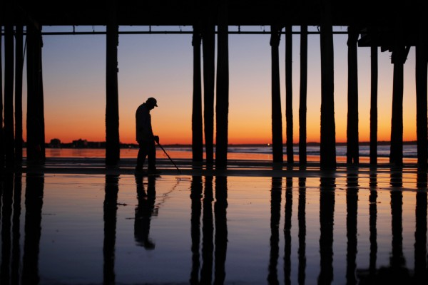 Jim Lantagne of Arundel, Maine, uses a metal detector to search for lost valuables under The Pier at dawn at Old Orchard Beach.