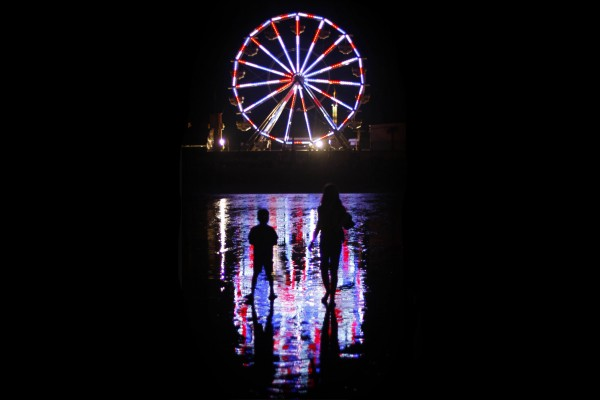 The colorful lights of Palace Playland's new Ferris wheel reflect on wet sand at Old Orchard Beach.
