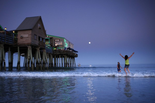 Beach-goers splash in the surf as the full moon rises at dusk at Old Orchard Beach.