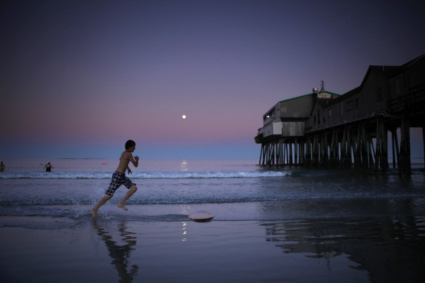 Canadian visitor Oliver Provencher skimboards as the full moon rises at dusk at Old Orchard Beach.