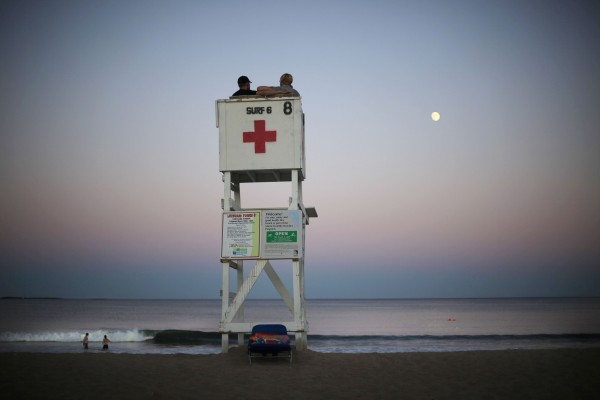 A couple watches the moon rise from a lifeguard's tower at dusk at Old Orchard Beach.