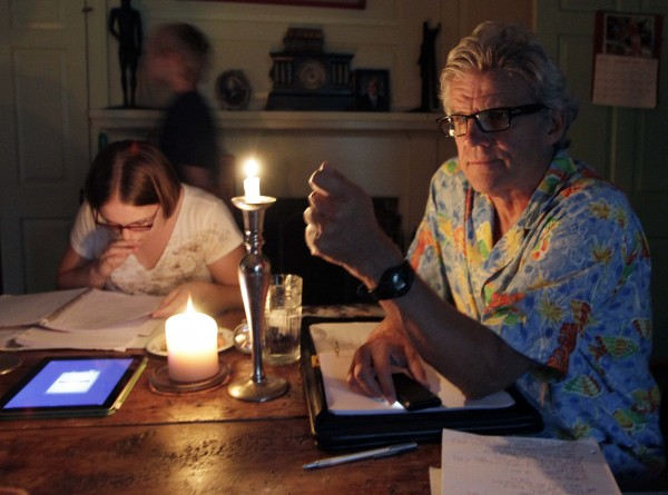 Academy Award-winner Ernest Thompson uses candles to go over the script after loosing power from a powerful thunderstorm in New Hampton, N.H. on Sunday, Aug. 21