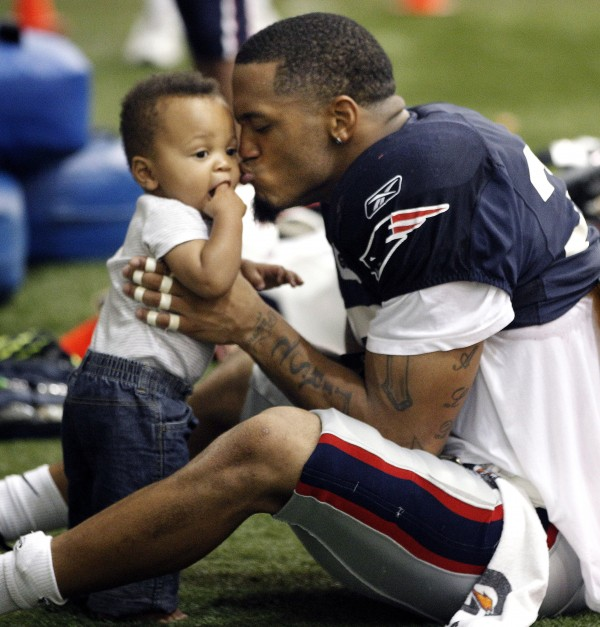 New England Patriots safety Pat Chung kisses his 11-month-old son during NFL football training camp Monday, Aug. 15, 2011,  in Foxborough, Mass.