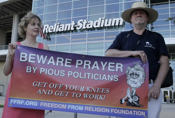 Annie Laurie Gaylor (left), president of the Freedom From Religion Foundation, and foundation member Rodney Hinds protest outside Reliant Stadium where The Response, a daylong prayer and fast rally is being held Saturday, Aug. 6, 2011, in Houston. Texas Gov. Rick Perry is speaking at the rally.