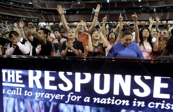 Participants sing and pray at The Response, a call to prayer for a nation in crisis, Saturday, Aug. 6, 2011, in Houston. Texas Gov. Rick Perry is scheduled to attend the daylong prayer rally despite criticism that the event inappropriately mixes religion and politics.
