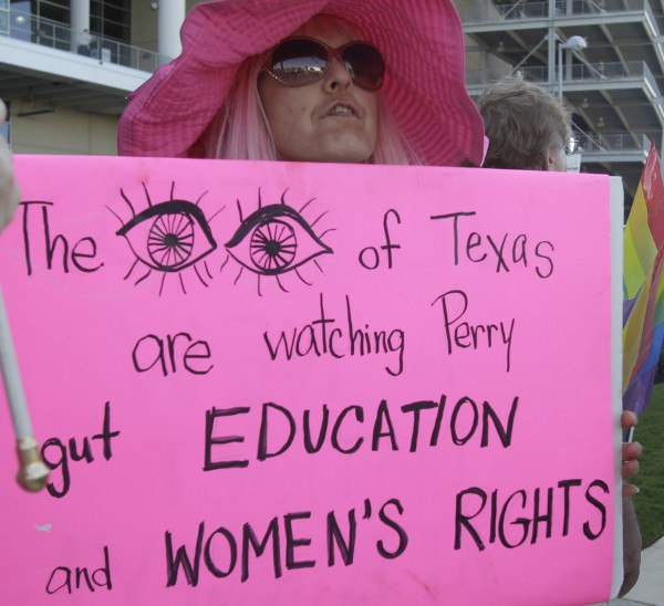 Shelley Buschur protests outside Reliant Stadium where Texas Gov. Rick Perry is speaking at The Response, a daylong prayer and fast rally, Saturday, Aug. 6, 2011, in Houston.