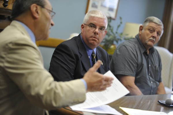 Milo police Sgt. Damien Pickel (center) listens as his attorney N. Laurence Willey (left) speaks on Pickel's behalf during a July, 26, 2011 press conference to discuss the dismissal of charges of domestic assault against Pickel. Listening at right is former Maine State Trooper Hank Dusenbery, a private investigator on the case. Milo Town Manager Jeff Gahagan confirmed Thursday, Aug. 4, that Pickel was reinstated at a selectmen's meeting on Tuesday night.