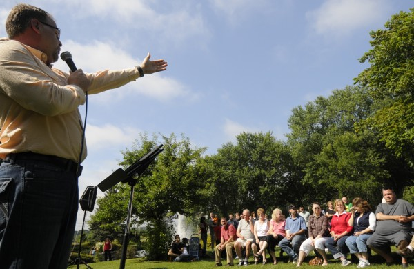 Pastor Matt Ward (left) of Charleston Pentecostal Church, speaks to fellow worshippers as they gather to pray for the nation at Cascade Park in Bangor on Saturday morning, Aug. 6, 2011.