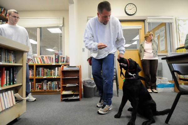Inmate Andy Pratt (center) of Rockland gets ready to offer 4 1/2-month-old Labrador retriever Sadie a reward after Sadie sat obediently for him and fellow Bolduc Correctional Facility inmate Joshua McCarthy (left) of Freeport. Sue Dumond (right), a classifications officer at the correctional facility in Warren, looks on.