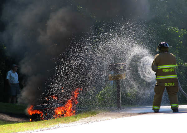 Rumford fire Lt. Sylvanus &quotButch&quot Glover douses a riding lawnmower that caught fire Friday afternoon when homeowner Ernest Phillips was mowing his lawn at 263 South Rumford Road in Rumford.