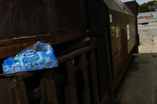 Bottled water packaging is wedged into a Dumpster behind the Shaw's supermarket on Main Street in Bangor last year. A pair of men were purchasing several cases of bottled water and then emptying the bottles in this holding dock area behind the supermarket so they could redeem the empty bottles for deposit money.
