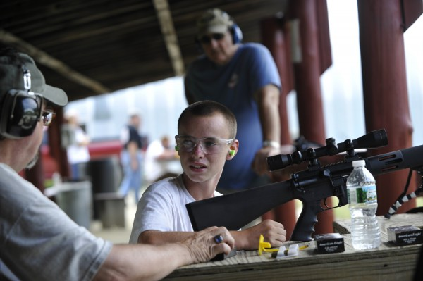 Austin Nute, 14, of Winterport gets a few pointers on how to properly handle a Bushmaster AR-15 from club member Dan Lawrence (seated left) as club president Ron Barron (in background) looks on during Saturday's open house event at the Hampden Rifle and Pistol Club.