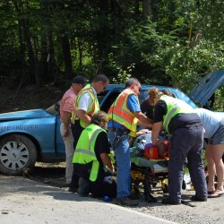 "Emergency responders assist Maine State Police Trooper Jedediah ""Jed"" Malcore of Wilton after he swerved to avoid a car that turned in front of his cruiser on Route 43 in Farmington while on his way to an accident in Weld."