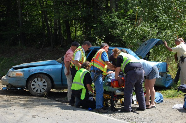Emergency responders assist Maine State Police Trooper Jedediah &quotJed&quot Malcore of Wilton after he swerved to avoid a car that turned in front of his cruiser on Route 43 in Farmington while on his way to an accident in Weld.
