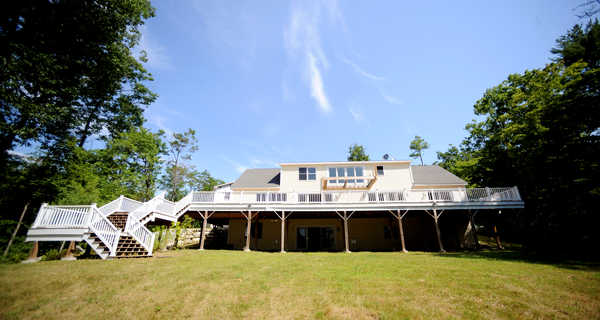 A deck runs the length of Dawn and Harvey Solomon's former home at 90 Zakelo Road in Harrison. The unfinished three-level house and three-bay garage will be sold at auction Aug. 30.