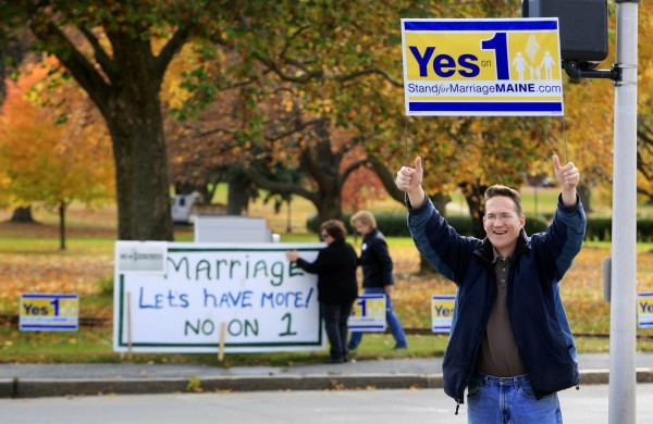 Joseph Skinner holds up a Yes on 1 sign to passing motorists while in the background supporters of same-sex marriage Ann DiMella and Suzanne Blackburn, of Portland, put up a No on 1 sign at Deering Oaks Park in Portland in November 2009.