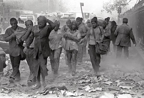 People covered in dust walk over debris near the World Trade Center in New York on Sept. 11, 2001.