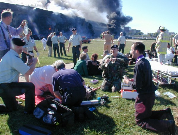 A priest prays over a wounded man outside the west entrance of the Pentagon on Sept. 11, 2001, as emergency workers from all services help the wounded after a terrorist attack on the Department of Defense building in Washington.