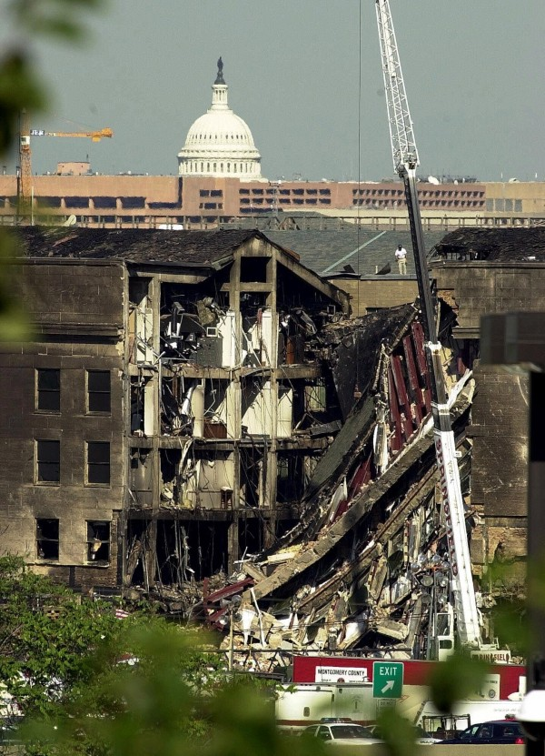Firefighters and inspectors look over the damage to the Pentagon in Washington one day after a hijacked airliner crashed into the Department of Defense building on Sept. 11, 2001. The dome of the United States Capitol is seen in the background.