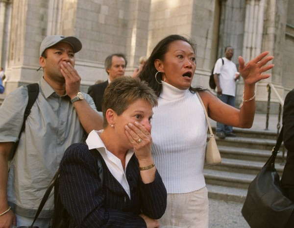 People in front of New York's St. Patrick's Cathedral react as they look down Fifth Avenue toward the World Trade Center after two airliners crashed into the twin 110-story buildings on Sept. 11, 2001.