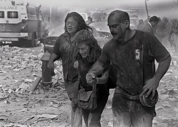 Julie McDermott (center) is helped by others as they make their way through the debris near the World Trade Center in New York on Sept. 11, 2001.