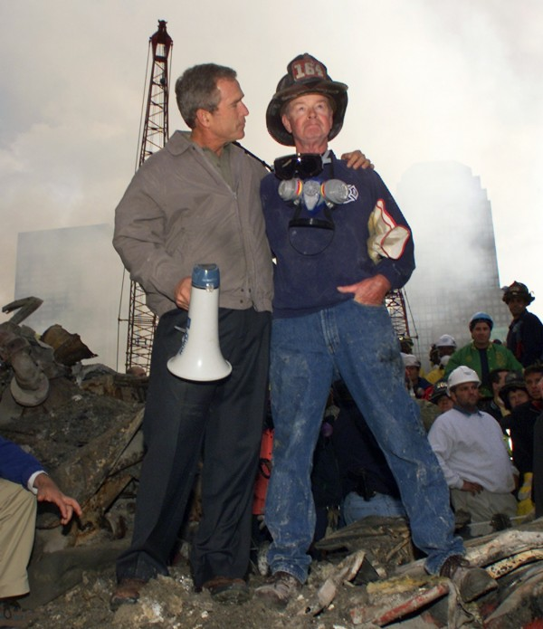 President George W. Bush embraces firefighter Bob Beckwith while standing in front of the collapsed World Trade Center buildings in New York as rescue efforts continue on Sept. 14, 2001.
