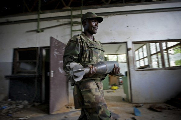 A Ugandan soldier serving with the African Union Mission in Somalia carries a shell that were used by the extremist group Al Shabaab to make improvised explosive devices in this photograph released by the African Union-United Nations Information Support Team on Monday, Aug.15, 2011. AMISOM troops and Transitonal Federal Government forces dislodged remnants of Al Shabaab from the site after the withdrawal of most of the extremist group's forces from the city 10 days ago, discovering the bomb-making facility at the former steel factory in northern Mogadishu which contained evidence that the group had used the site to manufacture improvised explosive devises, suicide vests and car bombs.