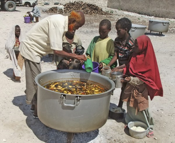 Children from southern Somalia receive cooked food in Mogadishu, Somalia, Monday, Aug 15, 2011. The World Food Program said Saturday that it is expanding its food distribution efforts in famine-struck Somalia, where the U.N. estimates that only 20 percent of people needing aid are getting it.
