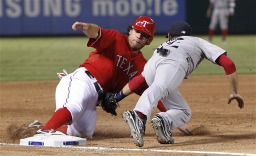 Ian Kinsler (left) of the Texas Rangers slides safely into third base ahead of the tag by Boston third baseman Jed Lowrie during the third inning of Monday night's game in Arlington, Texas. The Rangers shut out the Red Sox 4-0.