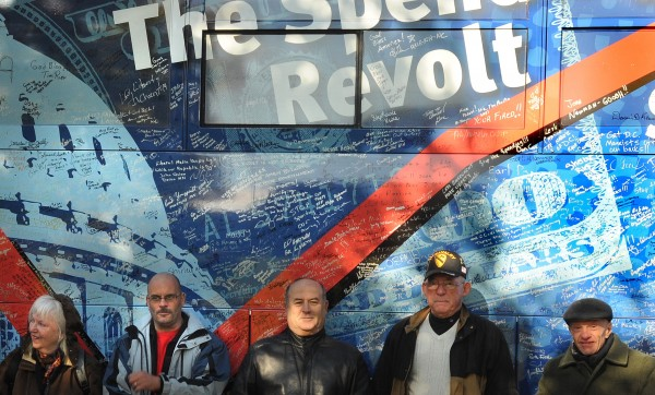People pose in the fron of the Spending Revolt bus in Paul Bunyan Park in Bangor for first of three scheduled stops in Maine.  The tour started in July in Las Vegas, Nevada and protests government spending. Over the months people from all over the country signed the bus to show their support.