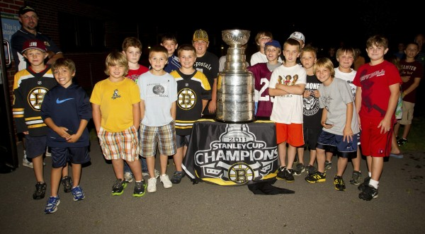 Members of the Bangor Youth Hockey Club pose with the Stanley Cup at a private aviation terminal in Bangor Friday night.
