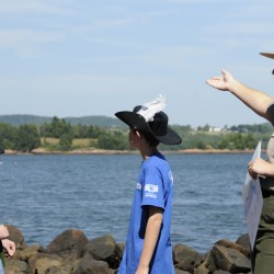 Standing on Red Beach, Lauren McGrath (right), a park ranger and language interpreter with the National Park Service, gestures towards St. Croix Island International Historic Site while giving visitors a history lesson  about the island on Aug. 1, 2011.