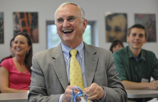 Past University of Maine President Robert Kennedy (center) reacts to warm farewell wishes as he opens gifts from colleagues during a campus gathering at the Foster Student Innovation Center on May 3.