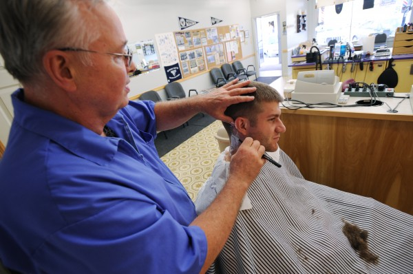 "University of Maine student Erik Vehr of Wellesley, Mass., gets his hair cut by Don Thomas of Erv's Barber Shop on Mill Street in Orono on Wednesday, August 31, 2011. Vehr says the price and service are great and the shop is close to the campus. ""It's a win in every way,"" he said."