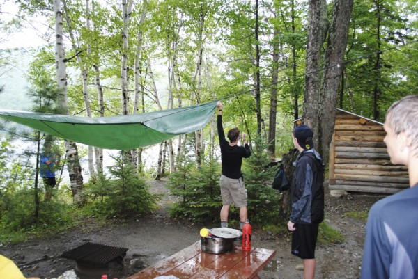Students in the Maine Youth Wilderness Leadership Program rig a tarp to keep off the rain at the lean-tos in South Branch Pond Campground.