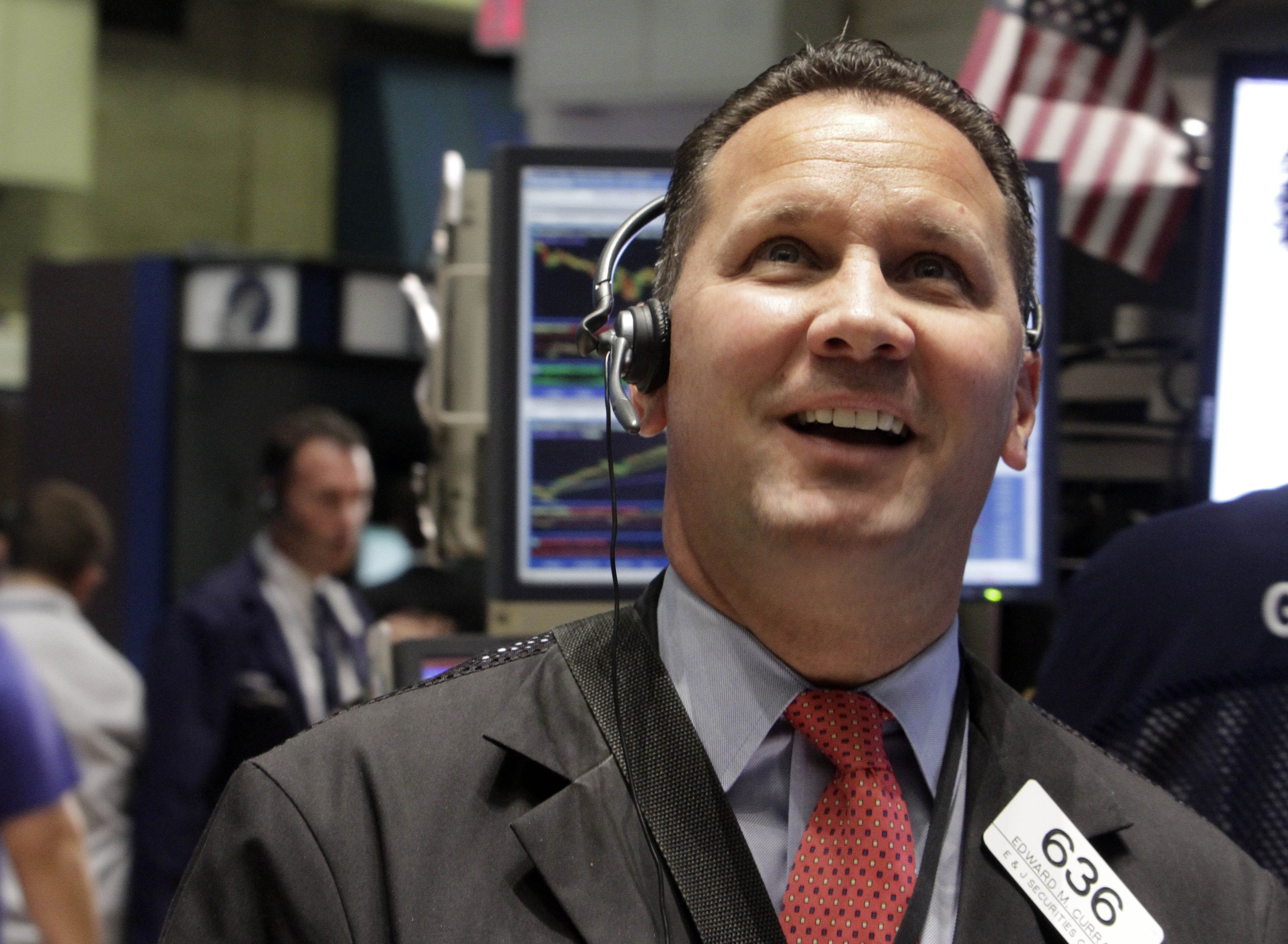 Trader Edward Curran smiles as he works on the floor of the New York Stock Exchange Thursday, Aug. 11, 2011.